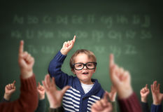 Standing out from the crowd at school. Elementary student school child with hand raised in the classroom in front of a blackboard with other children concept for Royalty Free Stock Photos