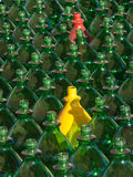 Standing out. Many green, one yellow and one red plastic bottle stock images