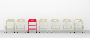 One red chair standing out in a row of chairs Royalty Free Stock Photo
