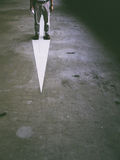 Standing on a painted arrow. A man standing on an arrow suggesting searching for the true path and reality Stock Photo