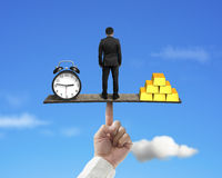 Standing person between clock and gold balancing on finger seesa Stock Image