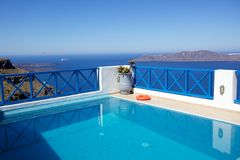 Standing by pool on top of Aegean Sea. Green plants sitting on the balcony with the Aegean sea as background Royalty Free Stock Photos