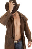 Standing put hat on duster. A man holding on to his western hat in his duster without a shirt stock photos