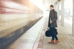 Standing on railway platform. Handsome young man with travel bag standing on railway platform outdoor, retro toned image Royalty Free Stock Image