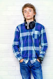 Standing relaxed boy. Modern teenage boy enjoys the music in headphones. Studio shot. Youth culture Stock Image