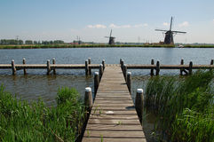 Standing by the River. A typically Dutch landscape, with windmills, a river and dykes Royalty Free Stock Image