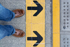 Standing on road with direction arrow Royalty Free Stock Photo