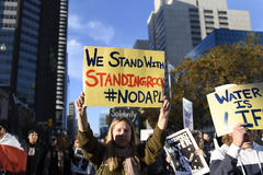Standing Rock protest in Toronto. TORONTO-NOVEMBER 5: A woman chanting slogans and with a banner saying `oil is not drinkable`during a solidarity rally with the Royalty Free Stock Image