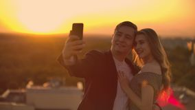 Standing on the roof at sunset a married couple a man and a woman hug and take a selfie on the phone. Take pictures of