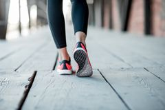 Standing in running shoes. Sports woman in running shoes standing back on the wooden floor, close-up view focused on the sneakers royalty free stock photo