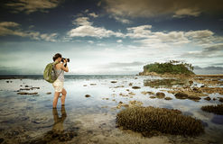 Standing in the sea water traveler woman with backpack taking a. Landscape of amazing far island on the horizon Stock Photos