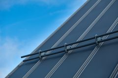 Standing seam metal roof. Close up with snow guards and blue sky in the background stock photo