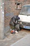 Standing while sleeping. A poor man sleeping standing in Bejing hutong royalty free stock image