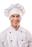Standing smiling male cook in white uniform and hat royalty free stock photography