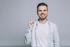 Standing smiling young man with beard in a white shirt Stock Images