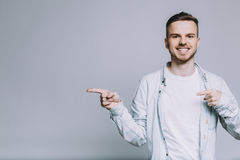 Standing smiling young man with beard in a white shirt Royalty Free Stock Photos