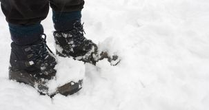 Standing in snow. Womans hiking boots covered in snow, closeup with copy space Royalty Free Stock Photos