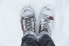 Standing in snow. Mans hiking boots covered in snow Stock Photo