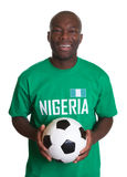 Standing soccer fan from Nigeria with ball Stock Images