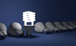 Standing spiral light bulb in row of lying ones on blue Royalty Free Stock Photo