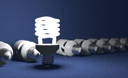 Standing spiral light bulb in row of lying ones Stock Photos