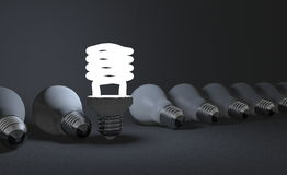 Standing spiral light bulb in row of lying ones on gray Stock Photo