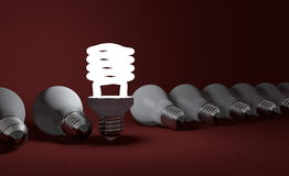 Standing spiral light bulb in row of lying ones on red Stock Images