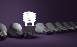 Standing spiral light bulb in row of lying ones on violet Stock Photos