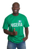 Standing sports fan from Nigeria showing thumb. Sports fan from Nigeria laughing at camera and showing thumb up on an isolated white background for cutout royalty free stock photo
