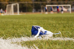Standing sports shoe on a background of  football field with the players. Selective focus. Royalty Free Stock Images