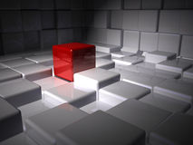 Standing In the Spotlight. A conceptual image of a single red cube standing in the spotlight in a room of white cubes Stock Images