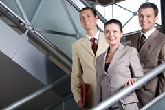 Standing on stairs. Portrait of positive business group standing on stairs of modern building Stock Image