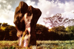 Standing Stone. Ancient standing stone with natural surroundings, forest and snowy mountains in the background Royalty Free Stock Photo