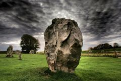 Standing Stone at Avebury Stone Circle Wiltshire UK. Standing stone at Avebury Ancient Stone Circle in Wiltshire UK on Green Grass with Stormy Grey Skies Stock Image