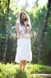 Standing in sun rays. Young romantic woman standing in sun rays Royalty Free Stock Image