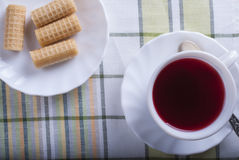 Standing on the table white Cup of tea hibiscus. The view from the top Royalty Free Stock Photo