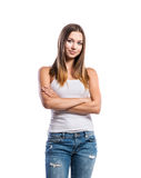Standing teenage girl in jeans and white singlet, isolated. Standing teenage girl in jeans and tight singlet, arms crossed, young woman, isolated on white royalty free stock photography