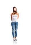 Standing teenage girl in jeans and white singlet, isolated. Standing teenage girl in jeans, tight singlet and sneakers, hands holding behind back, young woman royalty free stock photos