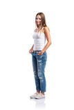 Standing teenage girl in jeans and white singlet,  isolated. Standing teenage girl in jeans, tight singlet and sneakers, hands in the pockets, young woman Stock Photo