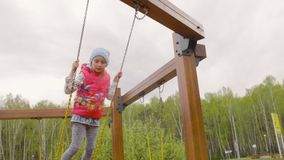Standing teenager girl swinging at spring day in city park slow motion stock footage