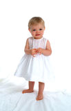 Standing Toddler Girl. Smiling, in white dress, on white background, barefoot, with hands together royalty free stock photo