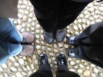 Standing together. Four people standing together in square, looking down vertical royalty free stock photo