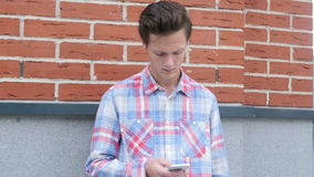 Standing by Wall, Man Using Smartphone. Creative designer , businessman stock video
