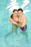 Standing in water. Photo of happy couple in swimming pool embracing and looking at camera Royalty Free Stock Photography