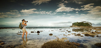 Standing in the water traveler woman with backpack taking a land Stock Photos