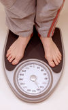 Standing on weight scale. Person standing on weight scale (face and torso not visible royalty free stock photo