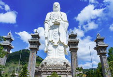 Standing white Buddha on a background of blue sky Royalty Free Stock Image