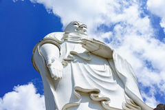 Standing white Buddha on a background of blue sky Stock Image