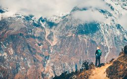 Woman with backpack on the path and mountains Stock Photo
