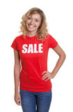 Standing woman with blond hair in a sale shirt Stock Photos